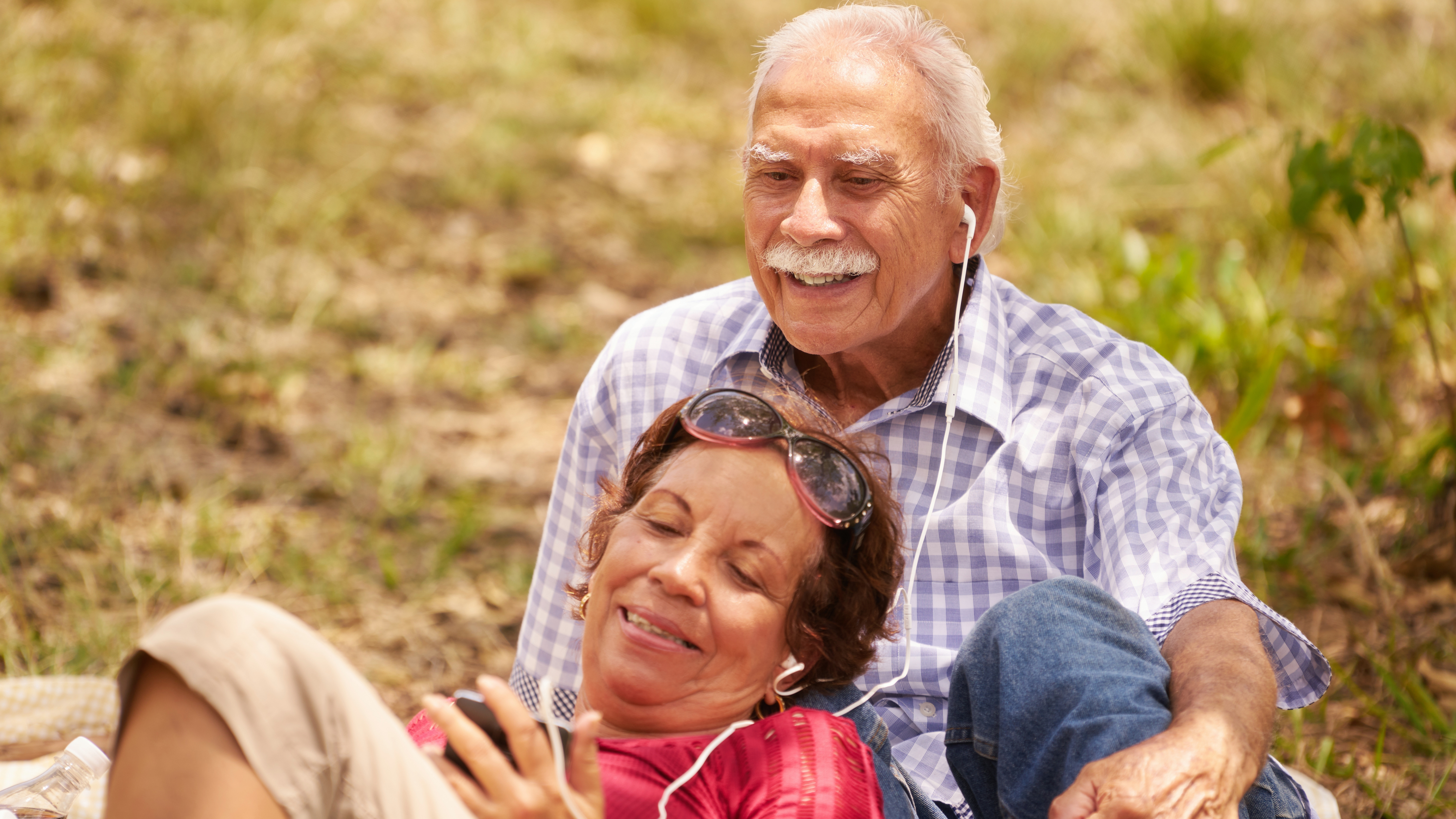 a senior couple, an elderly man and woman in park listening to music with earbuds or headphones