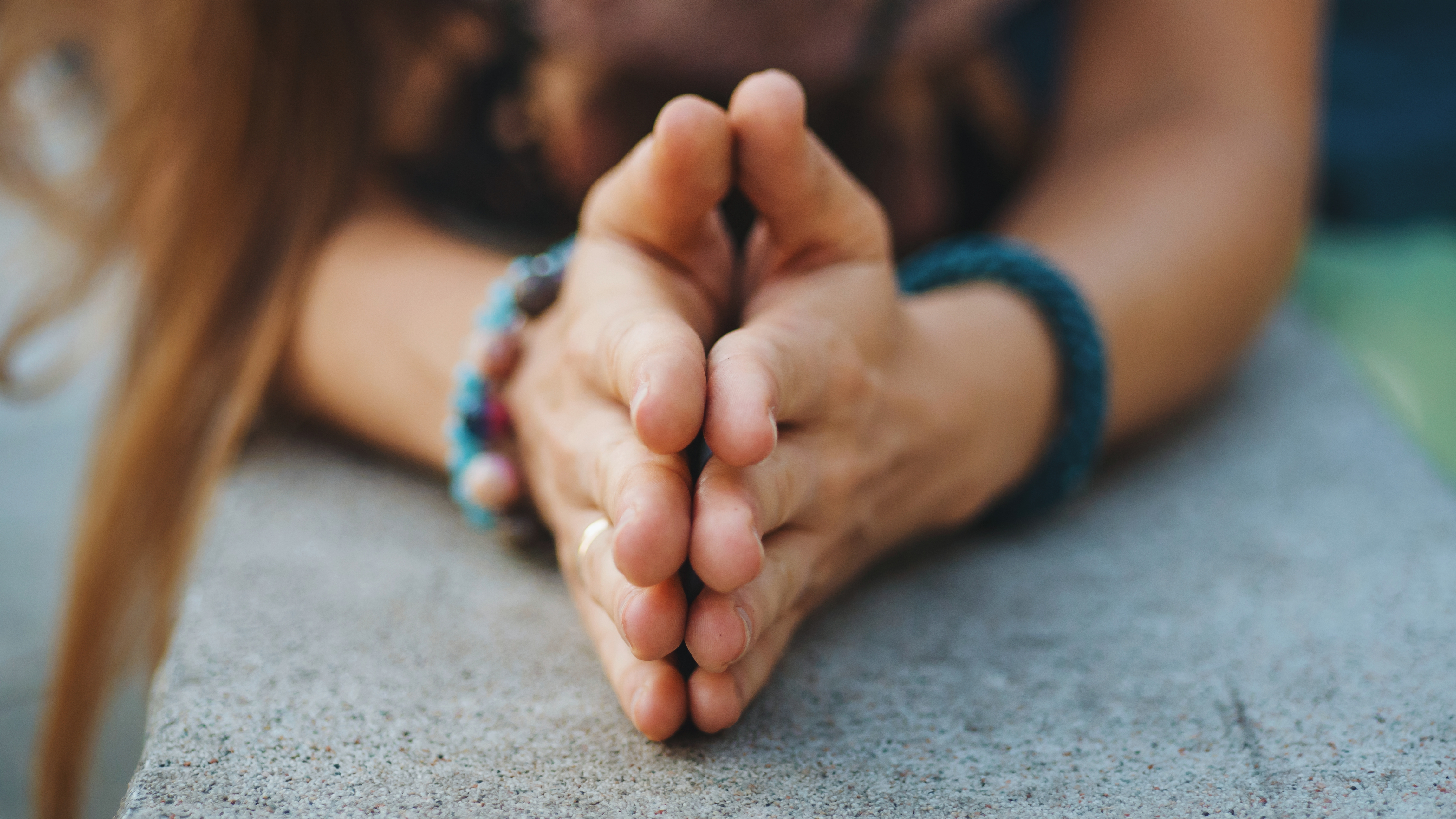 a young women's hands clasped together in a sign of prayer - wearing colorful bracelets