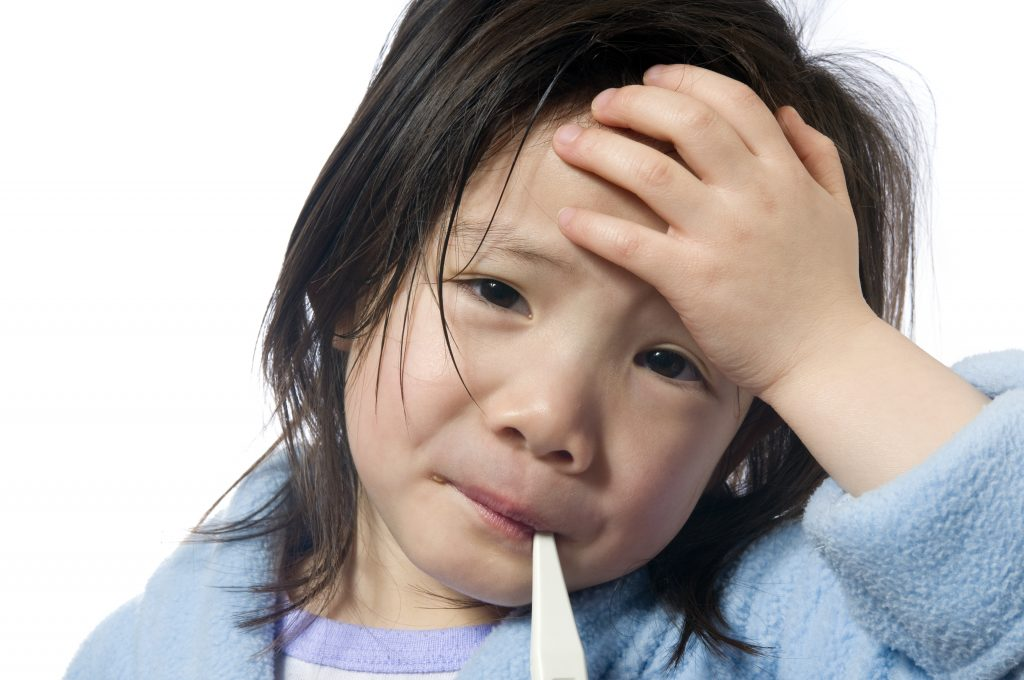 close-up of a little girl sick with fever, cold, flu, holding her forehead and having her temperature taken