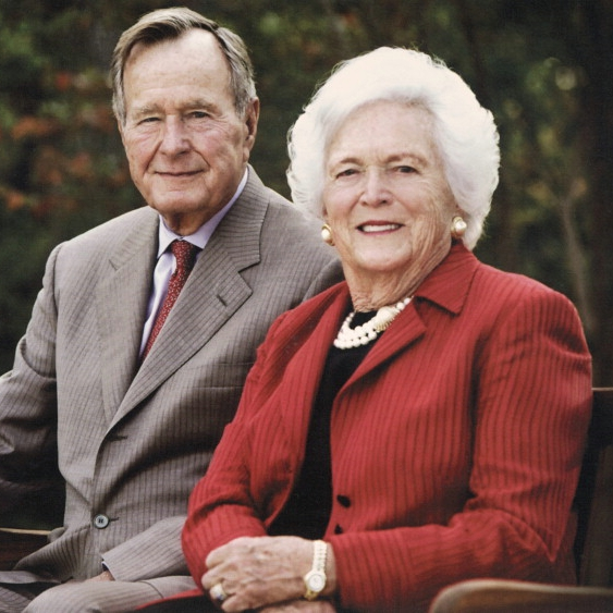 President H.W. Bush and his wife Barbara smiling and sitting outside on a bench