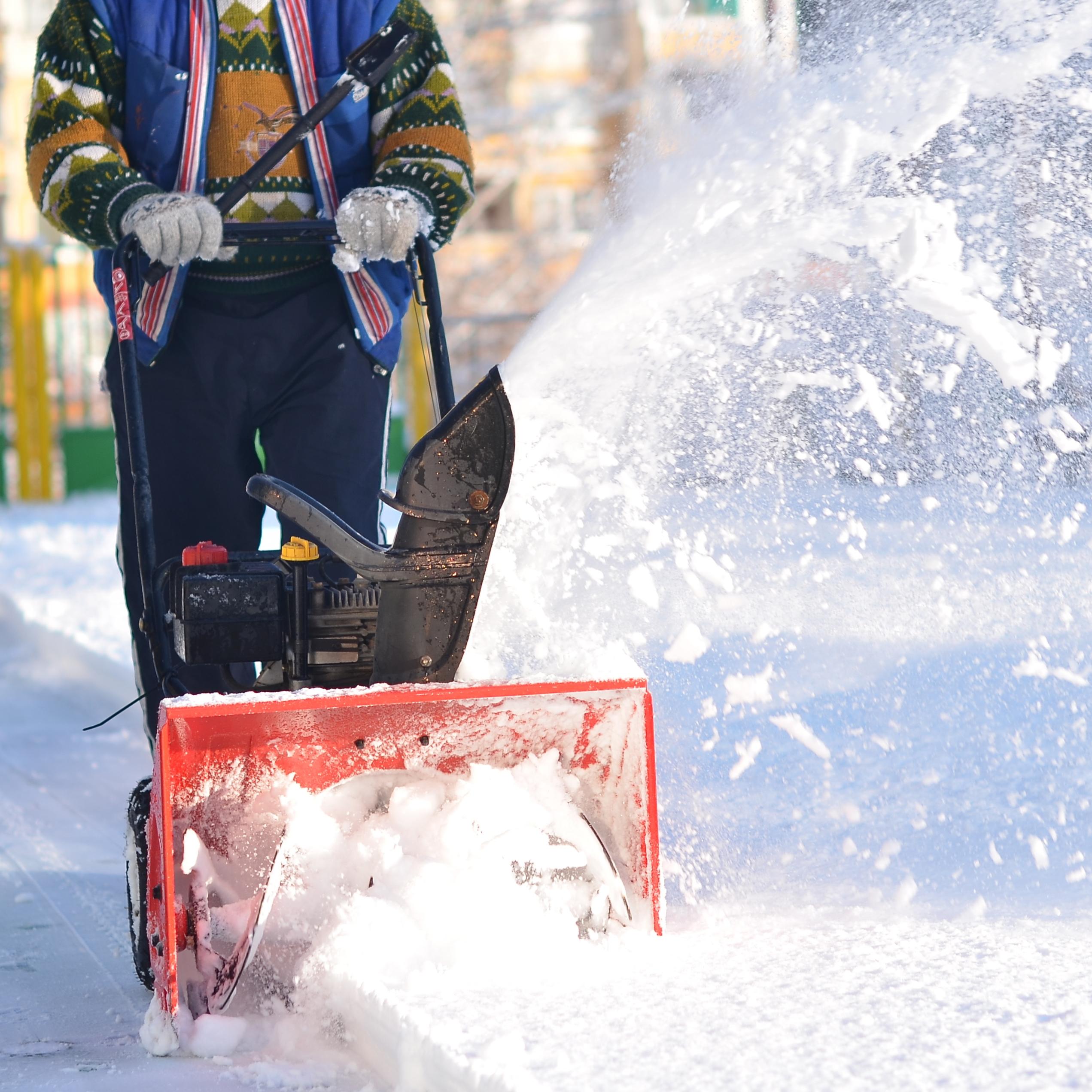 A man pushing a snowblower down a sidewalk.