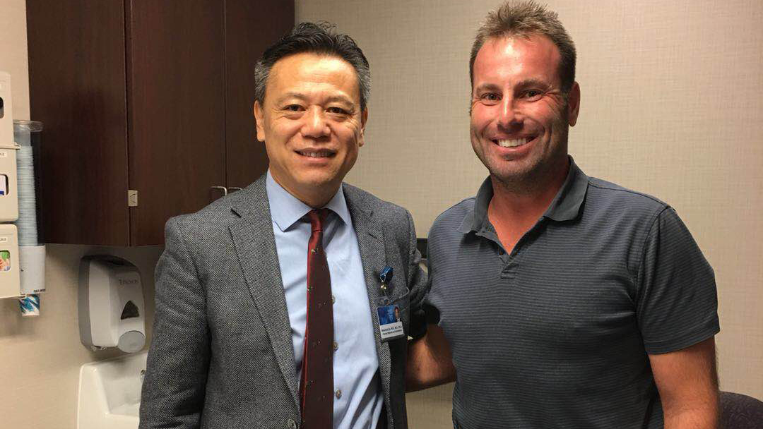 Sharing Mayo Clinic patient Rick Amatuzio smiling with Dr. Qu in an exam room
