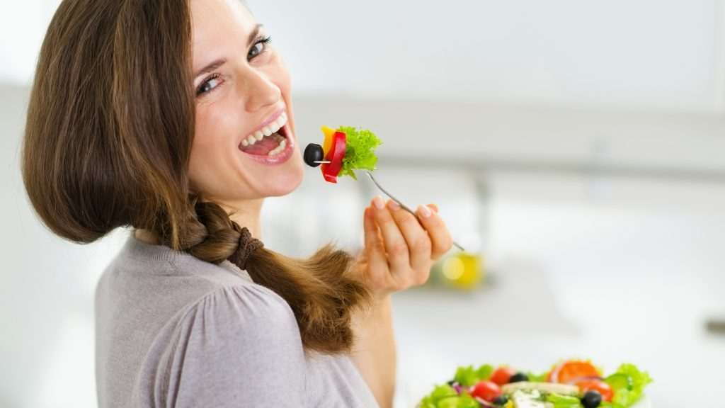 Una mujer sonríe y come una ensalada fresca en una cocina moderna
