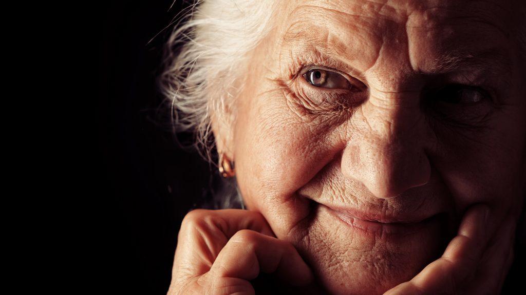 Acercamiento de una mujer mayor con mitad de la cara en la sombra que sonríe, pero da la impresión de estar confundida o preocupada