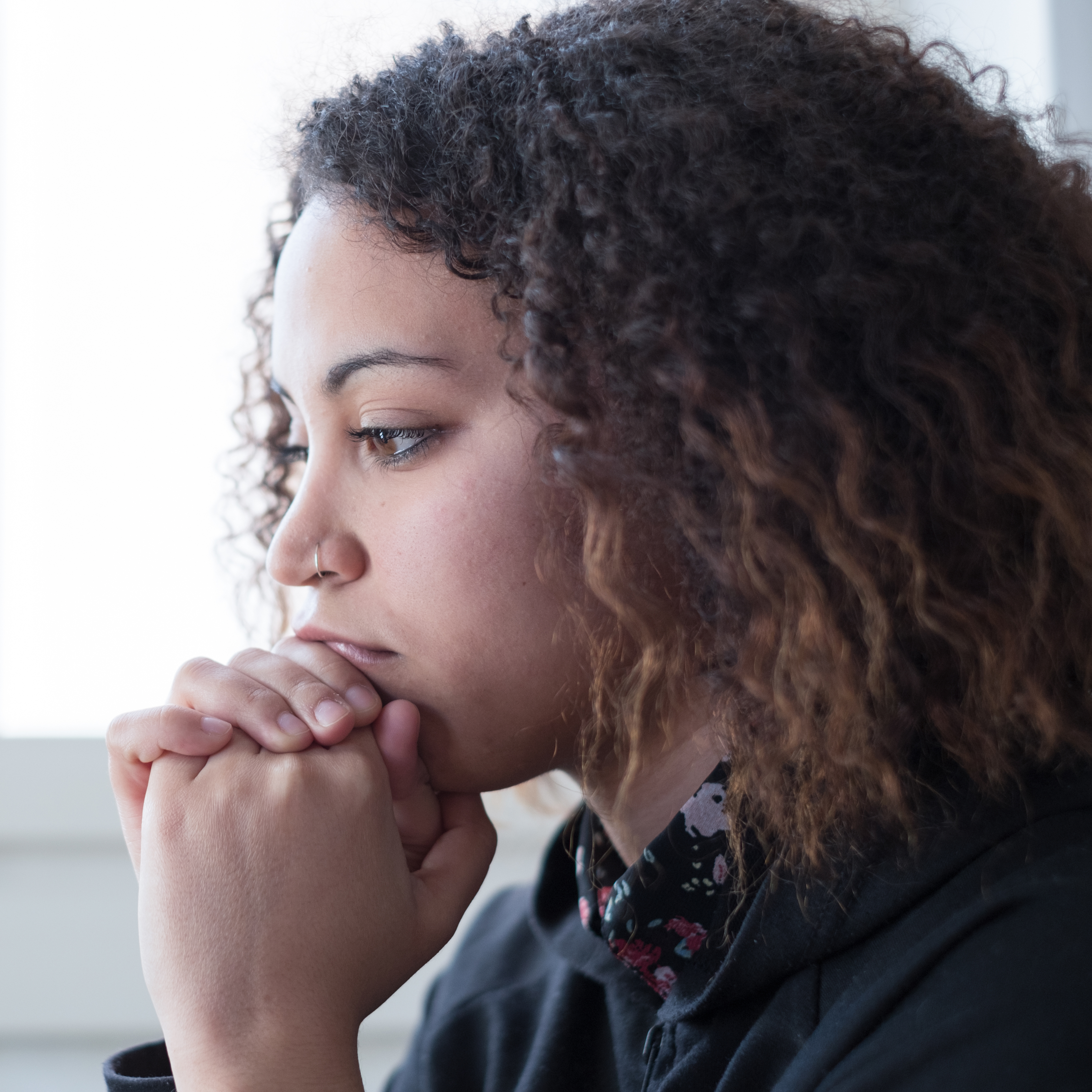 a profile close-up of a young woman, staring into space and sad and looking lost in thought, with her chin in her hands