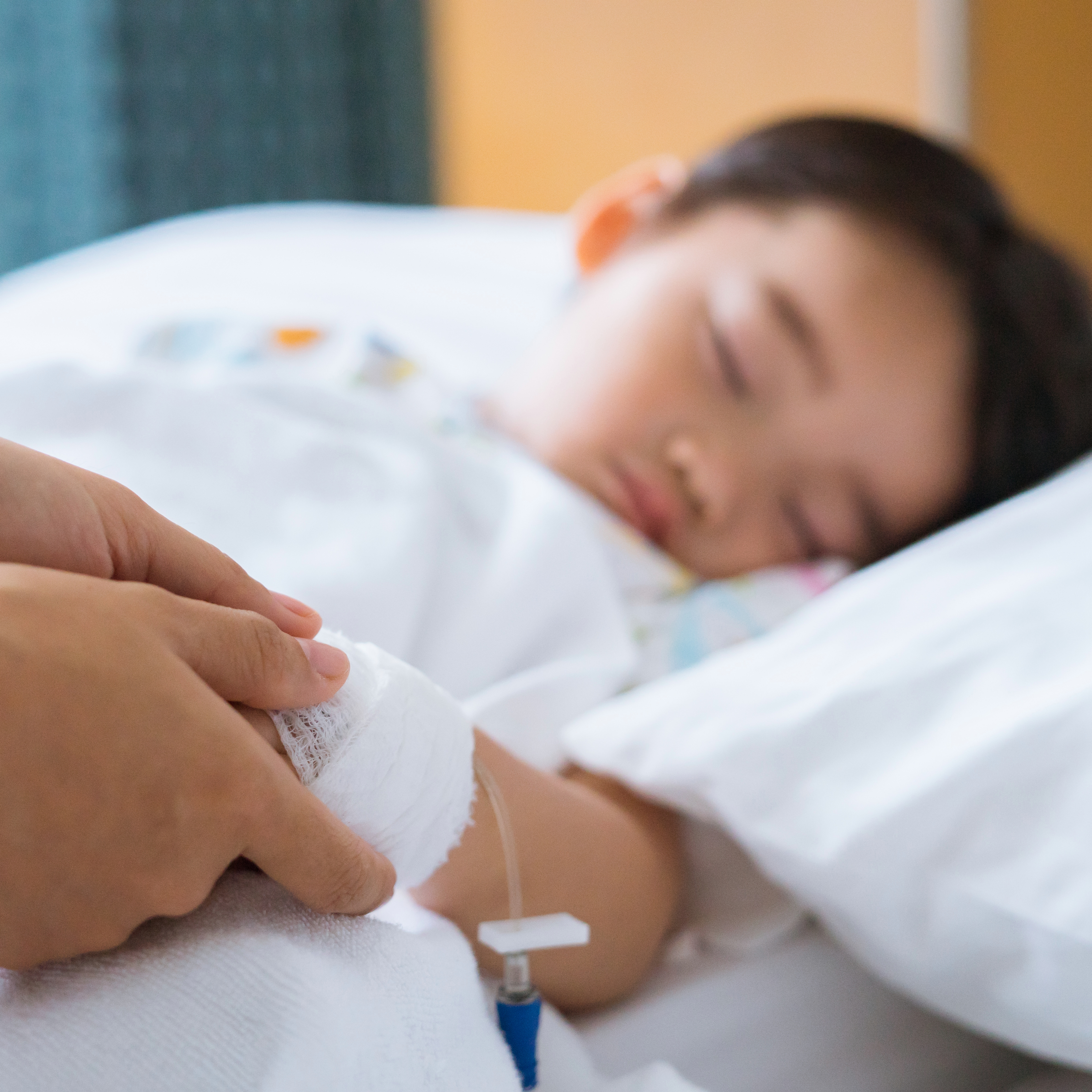 a sick little boy lying in a hospital bed with a bandage and IV and an adult holding his hand to comfort him