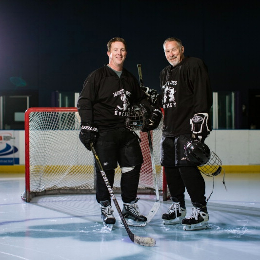 Donn D. Dexter, M.D., a neurologist, and Patrick L. Roberts, D.P.M., chair of the Division of Podiatry Mayo Clinic Health System on the ice in hockey gear