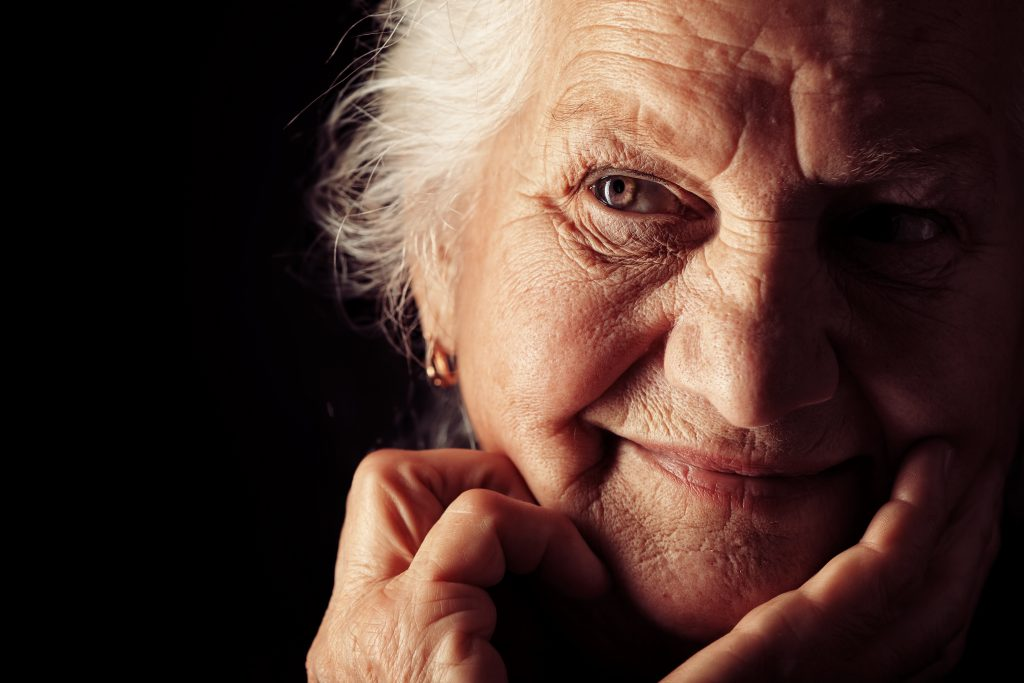 a close-up of an older woman, with her face half in shadow, smiling but looking a bit confused or worried