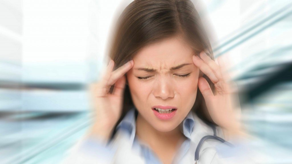 a young woman with her hands to her head in extreme pain from a headache or migraine