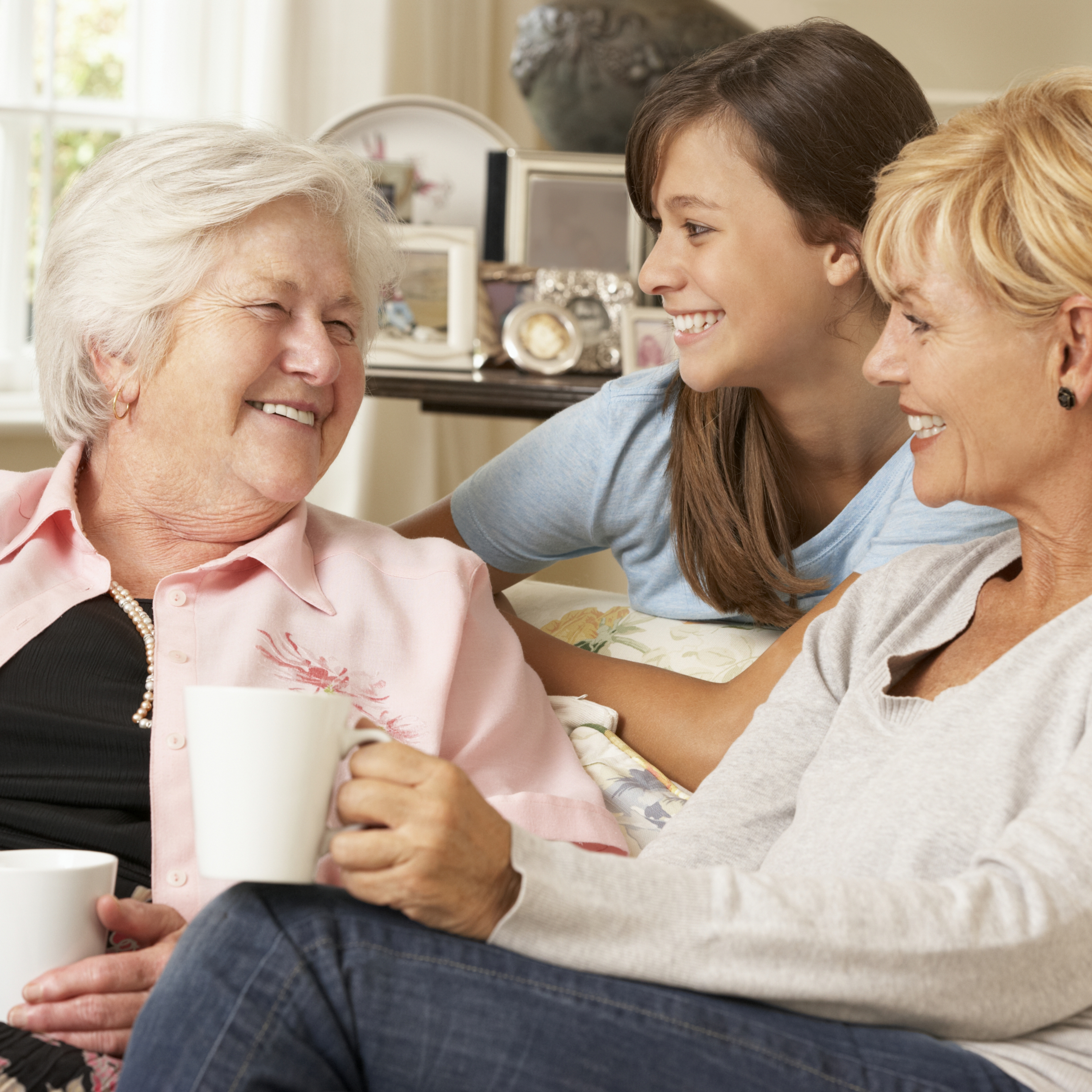 a three generational group of women smiling and having coffee together