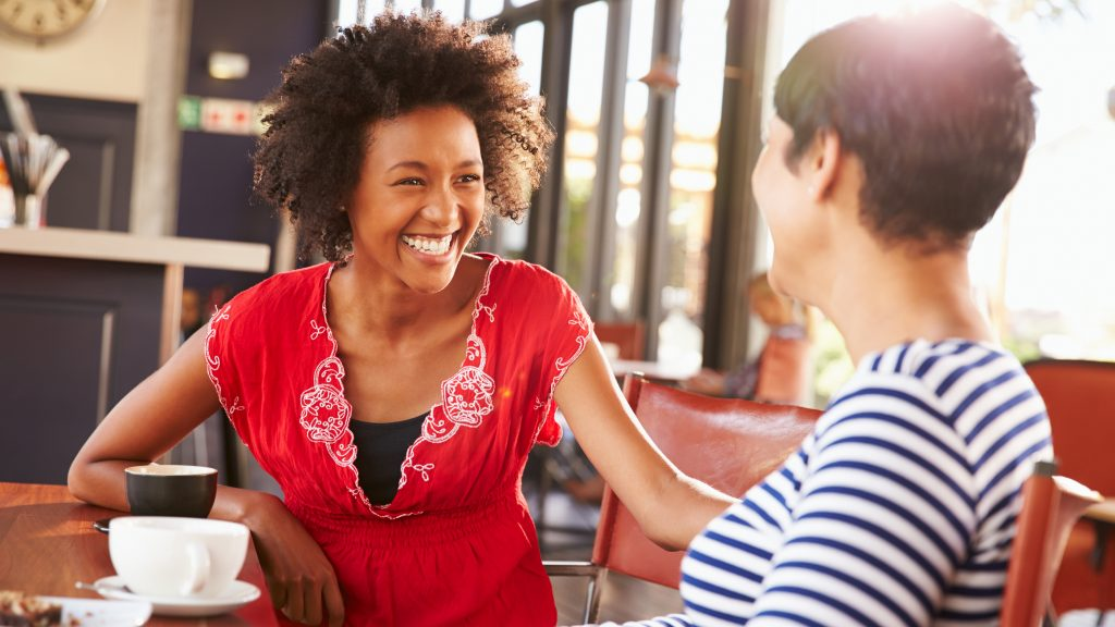 two female friends laughing and smiling over a cup of coffee in a restaurant