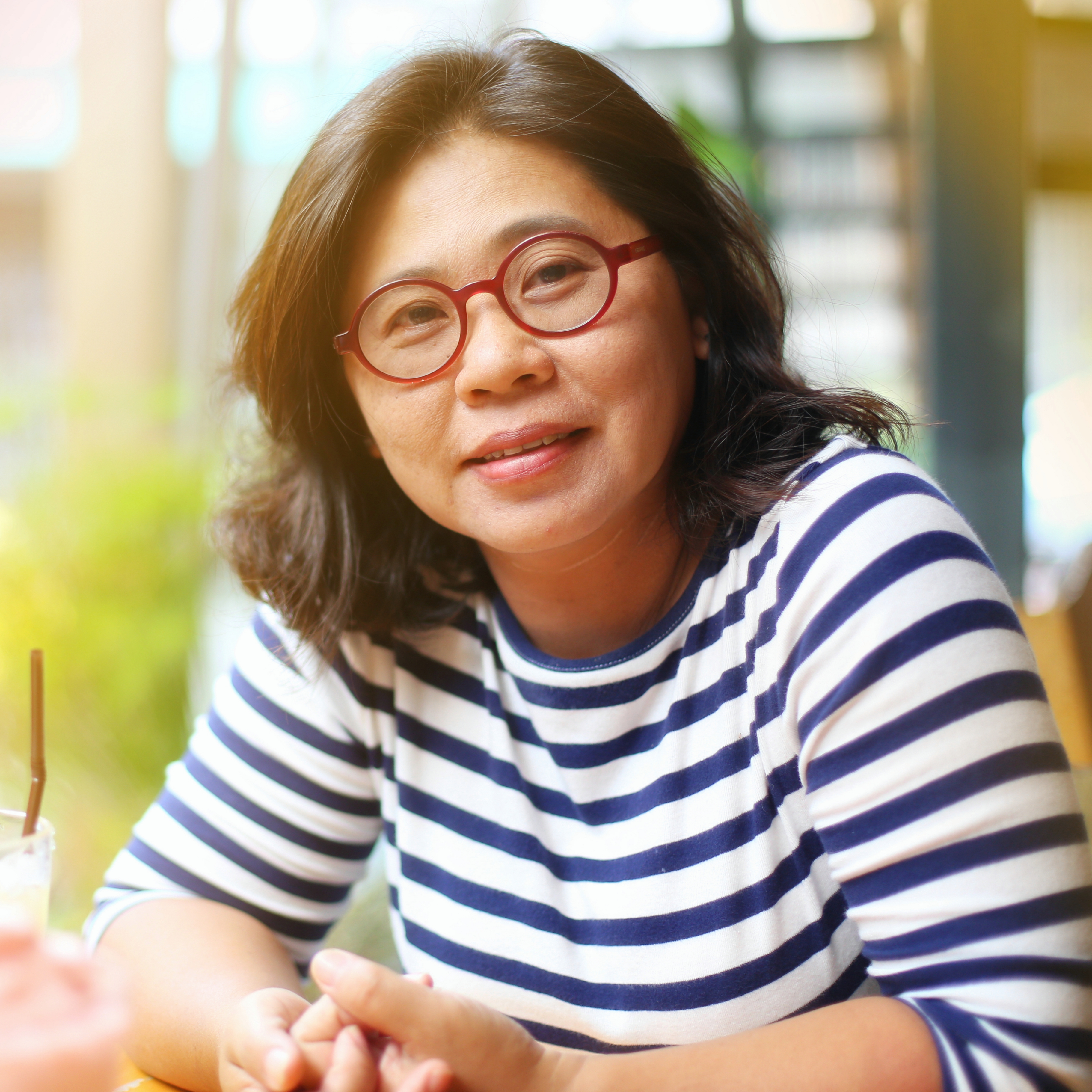 a mature or middle-aged Asian woman wearing glassed and sitting outdoors smiling, looking content and happy