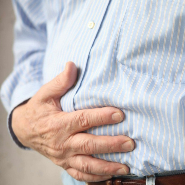 a man holding his stomach as if in pain with a stomach ache, intestinal problems