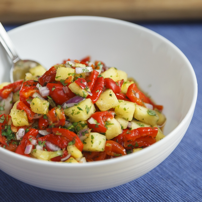 a white bowl of red pepper pineapple salsa with a spoon