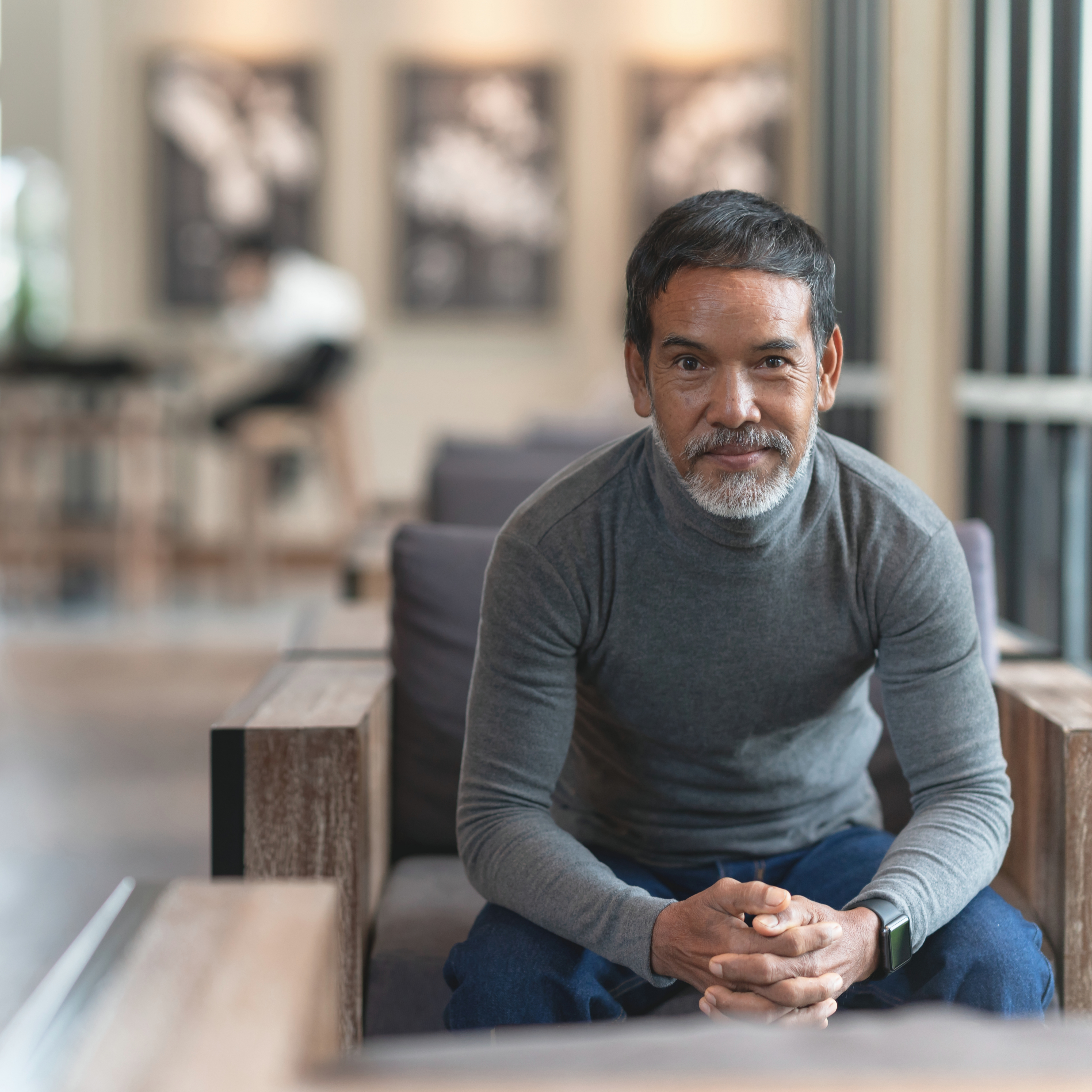 Portrait of mature man with confident smile and white stylish short beard looking at camera sitting in modern coffee shop.
