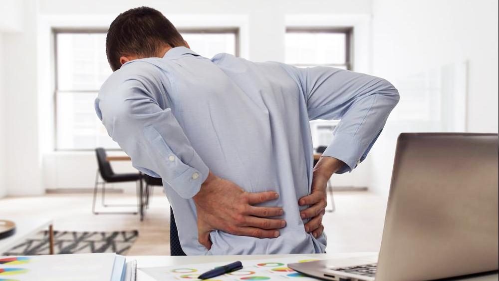 Un ejecutivo sentado en el escritorio con dolor de espalda