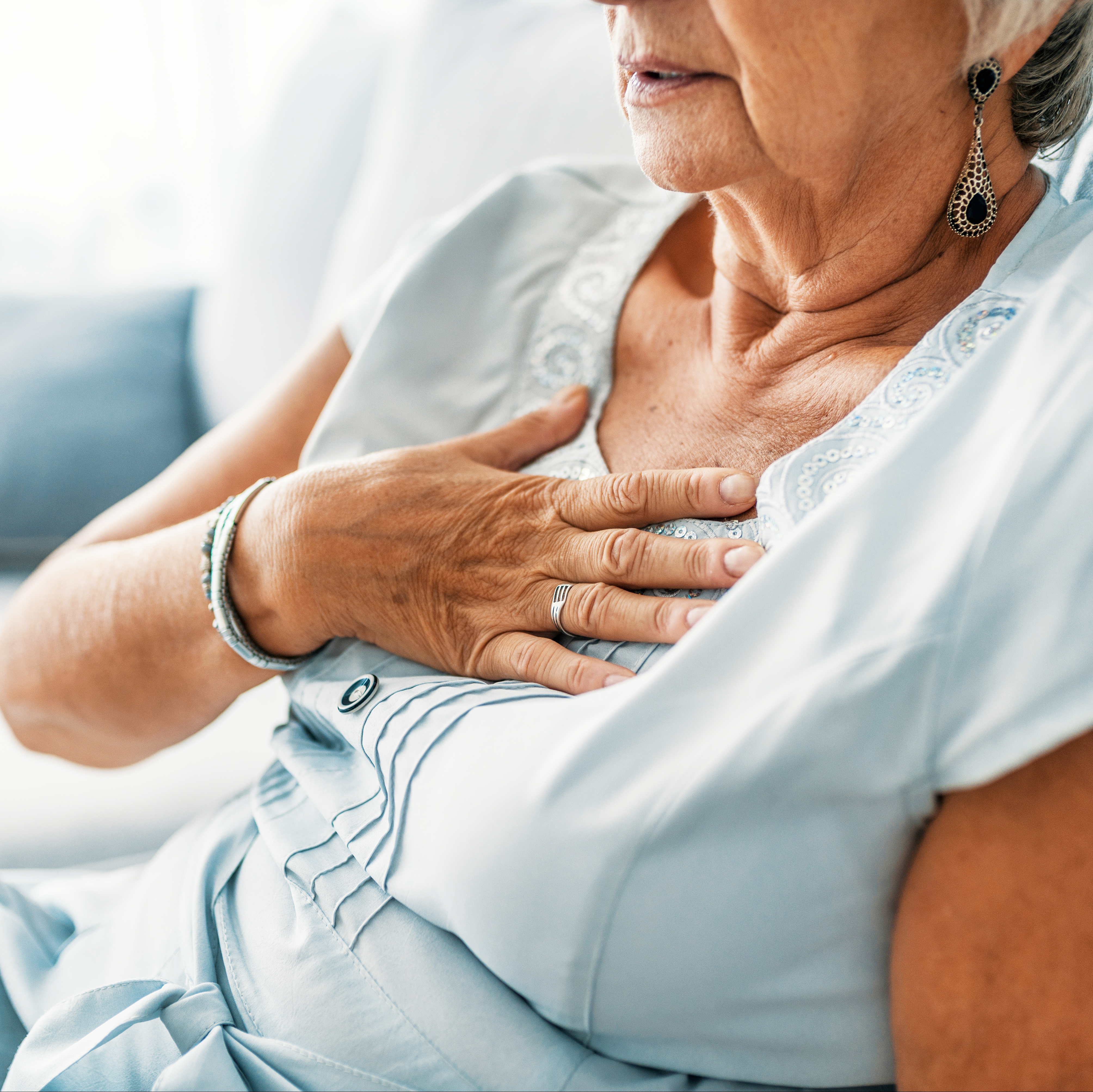 a middle aged woman holding her hand to her chest in pain, as if she's having a heart attack