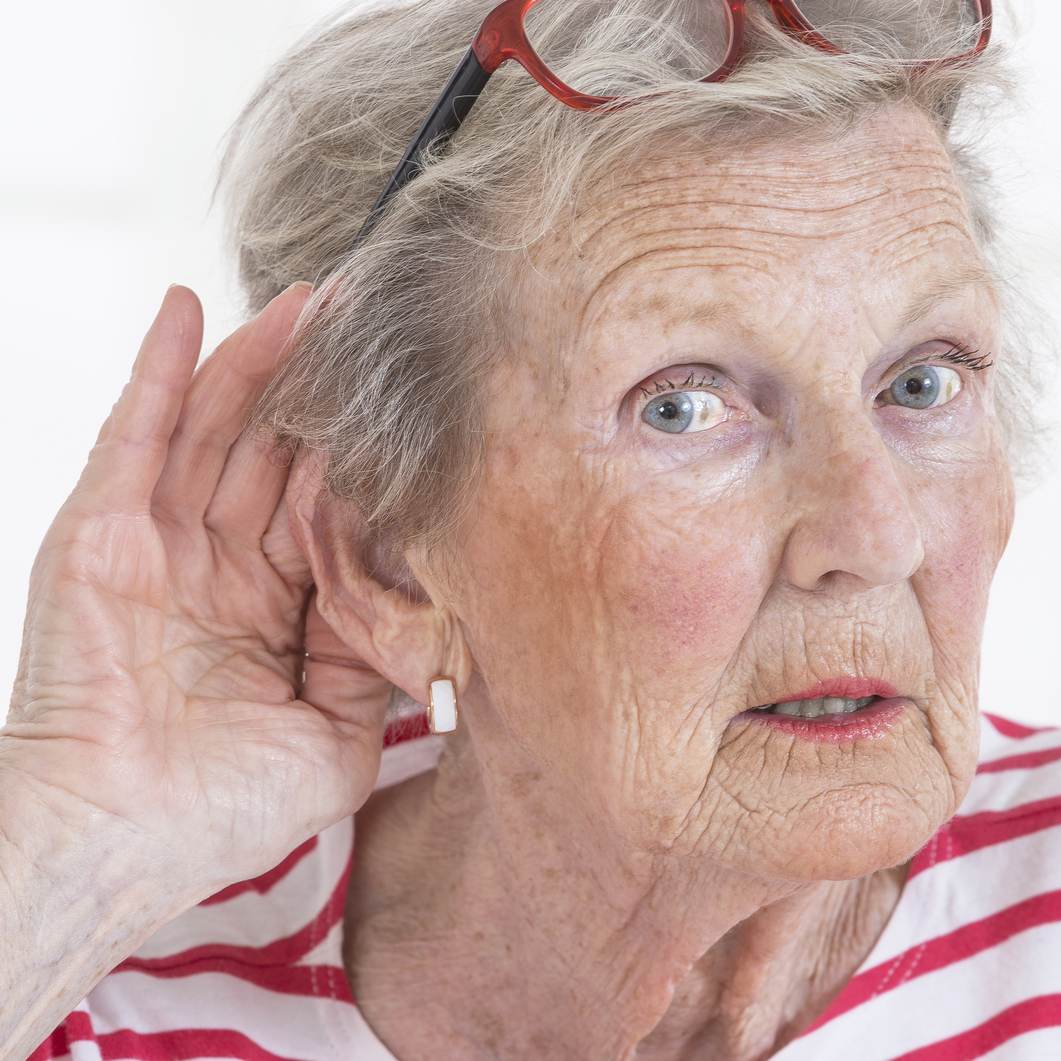 an older or middle-aged woman holding her hand to her ear trying to listen and hear something