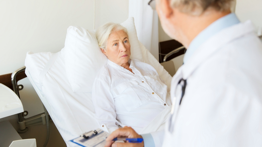 Senior woman and doctor writing on clipboard in hospital ward