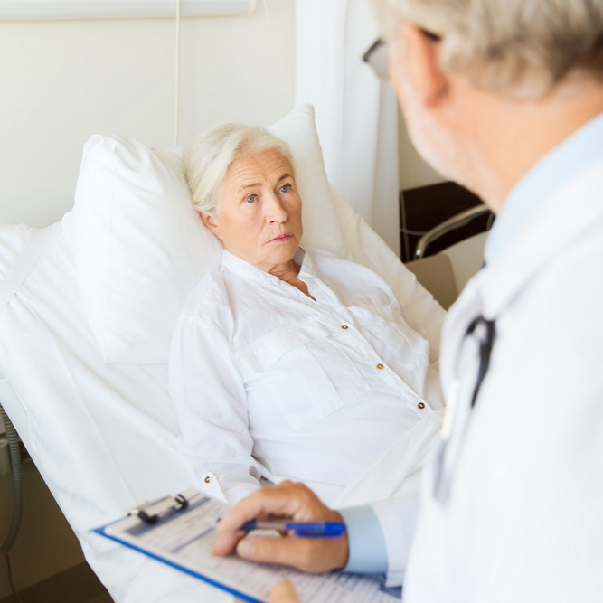 Senior woman and doctor writing on clipboard in hospital room