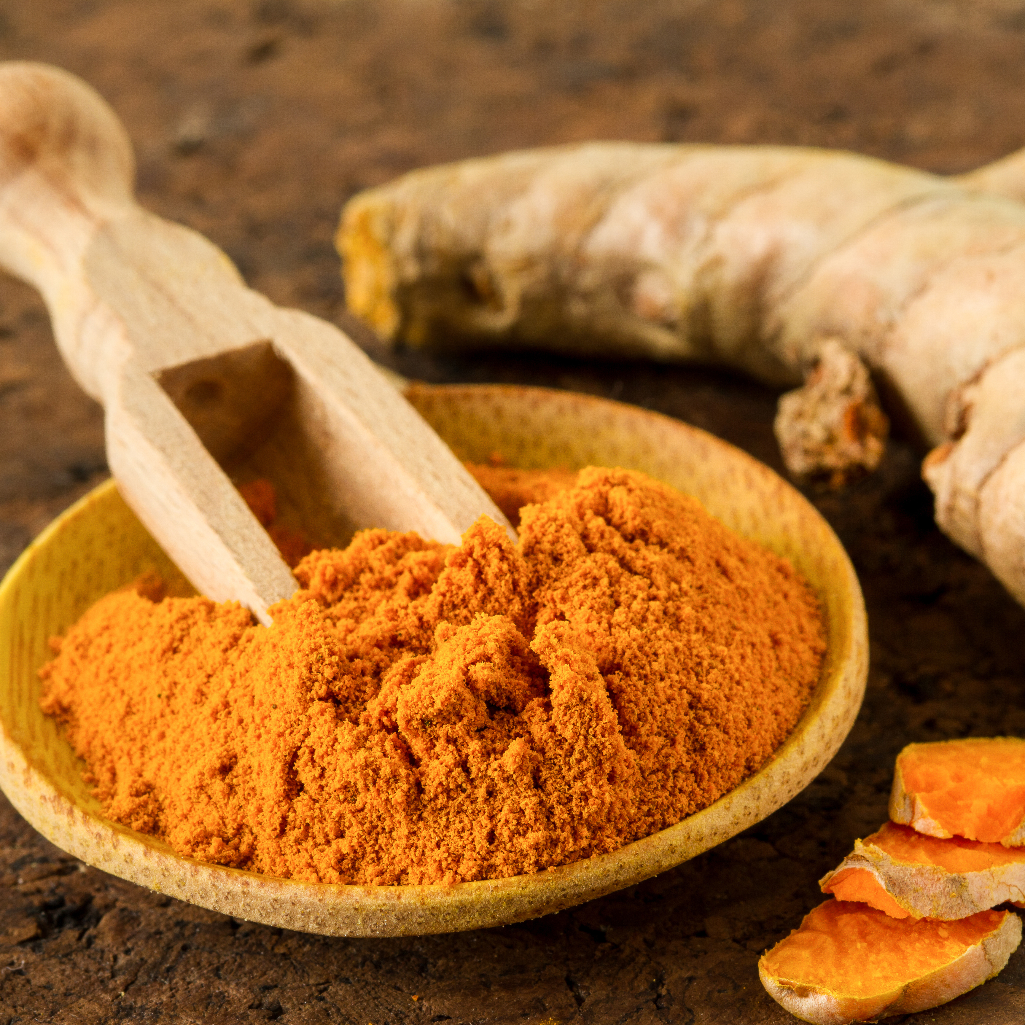 a small wooden bowl of ground turmeric and some whole turmeric root on a rough wooden surface