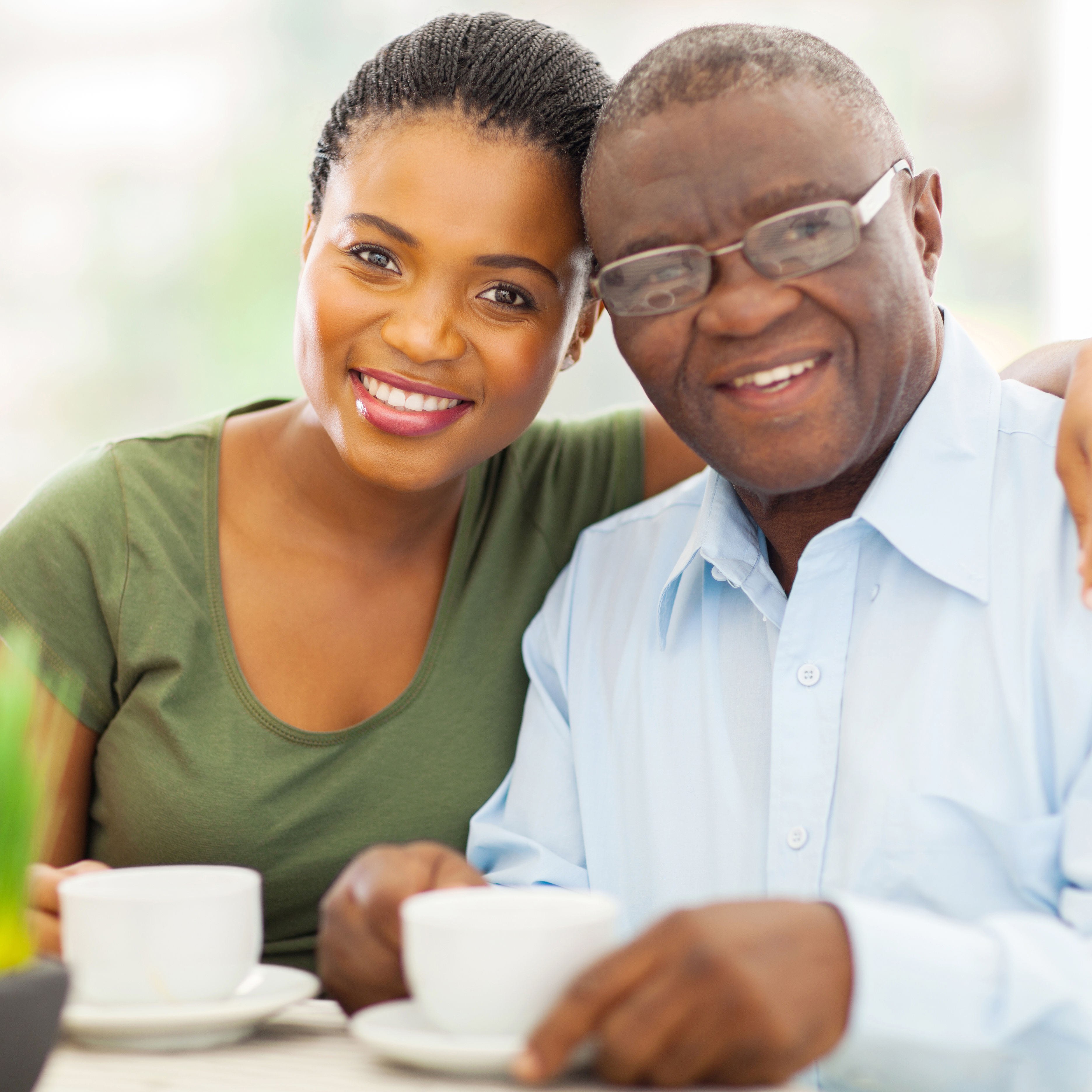 a smiling elderly father and his adult daughter, with cups of tea or coffee
