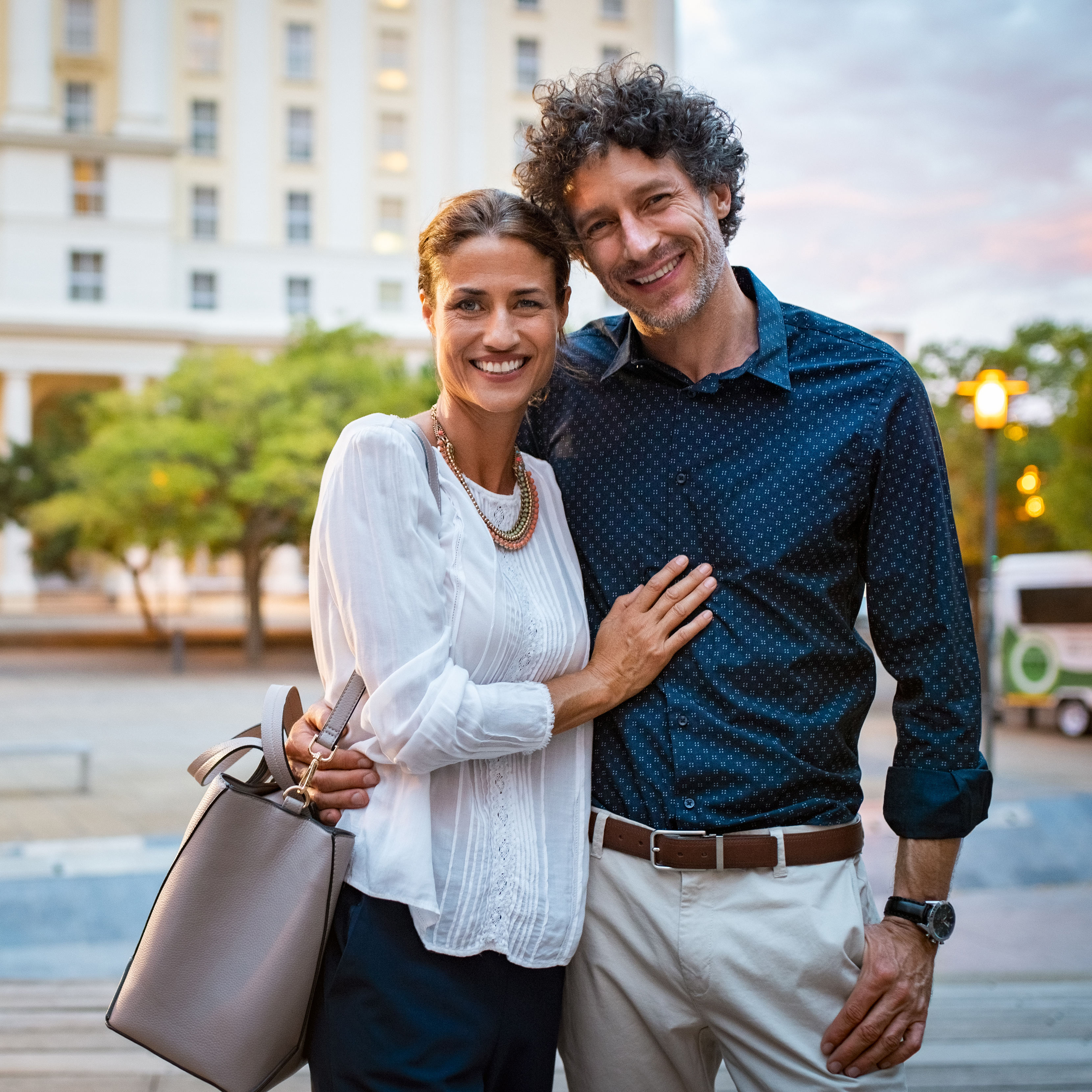 a smiling middle-aged couple, standing together in an outdoor city plaza