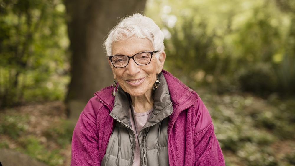 Una mujer mayor está afuera y sonríe