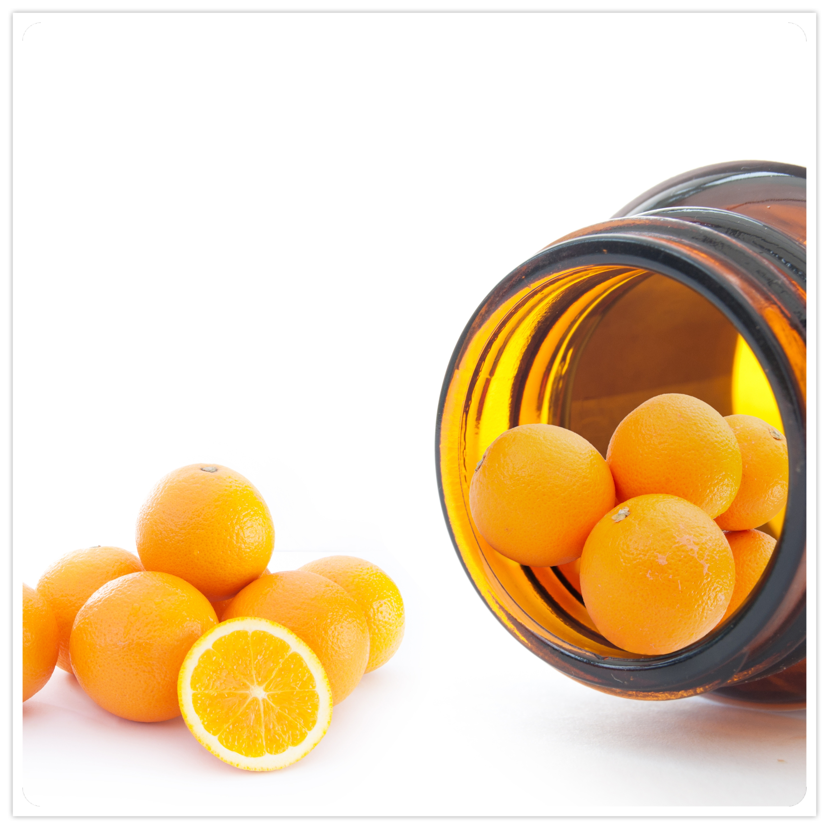 an open pill bottle on its side, spilling out oranges - vitamin C concept