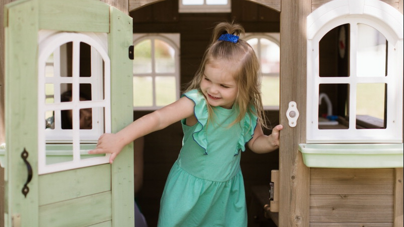 cancer patient Reese Buntenbach smiling and playing in her small playhouse