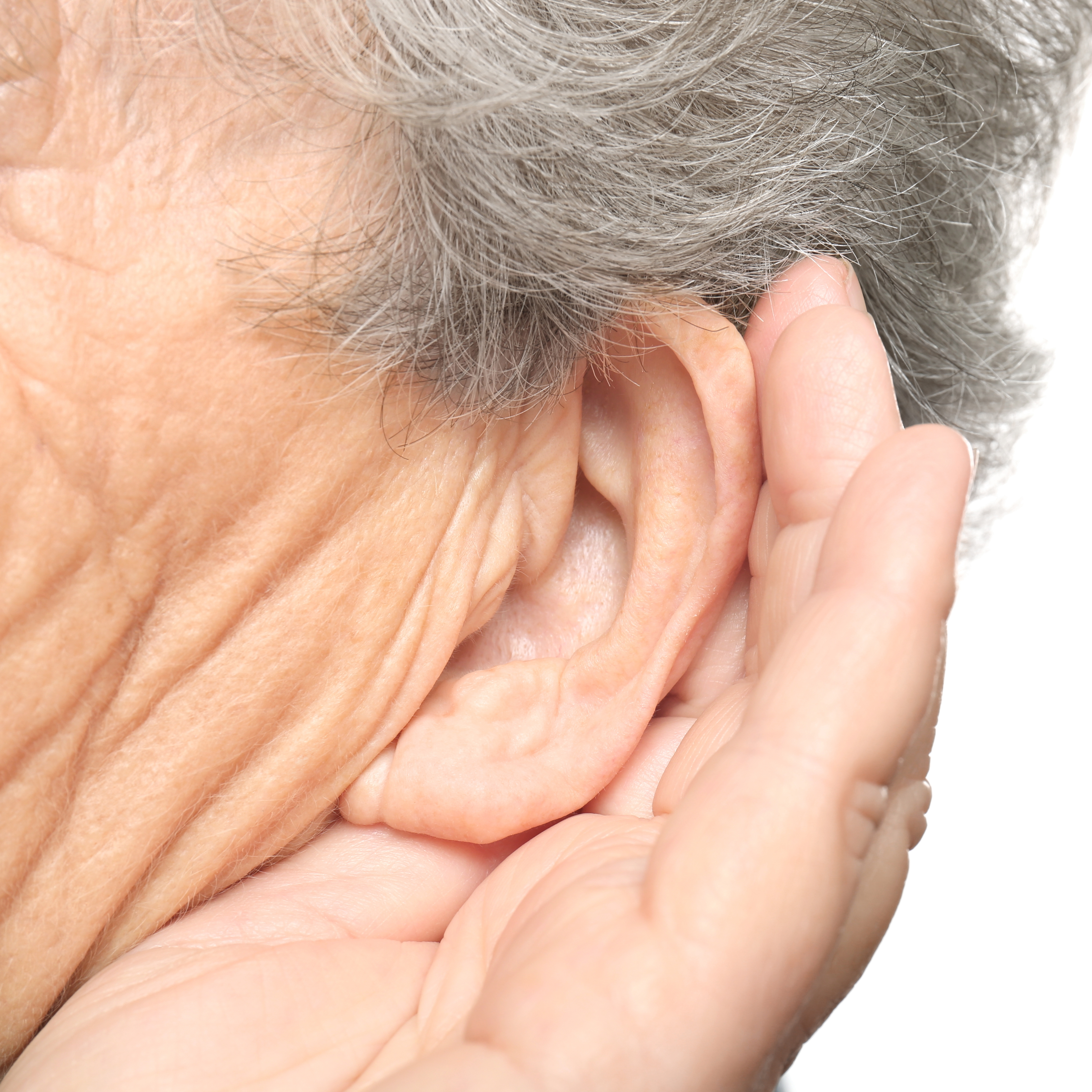 an older or middle-aged person hard of hearing, holding their ear and trying to listen