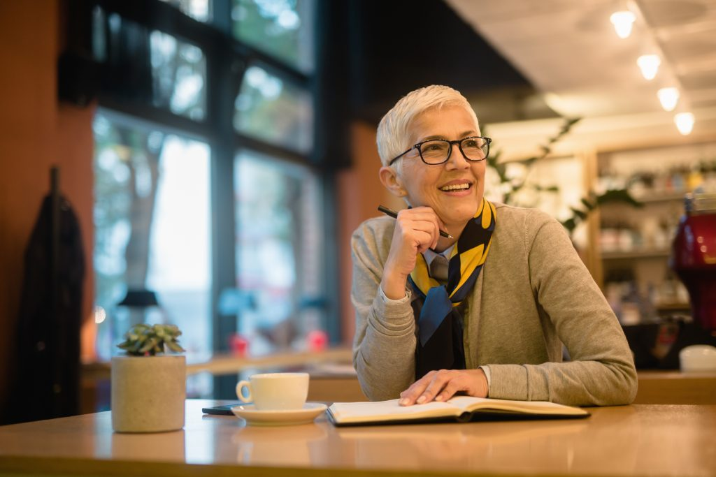 a smiling senior woman, sitting in a coffee shop, writing in a journal