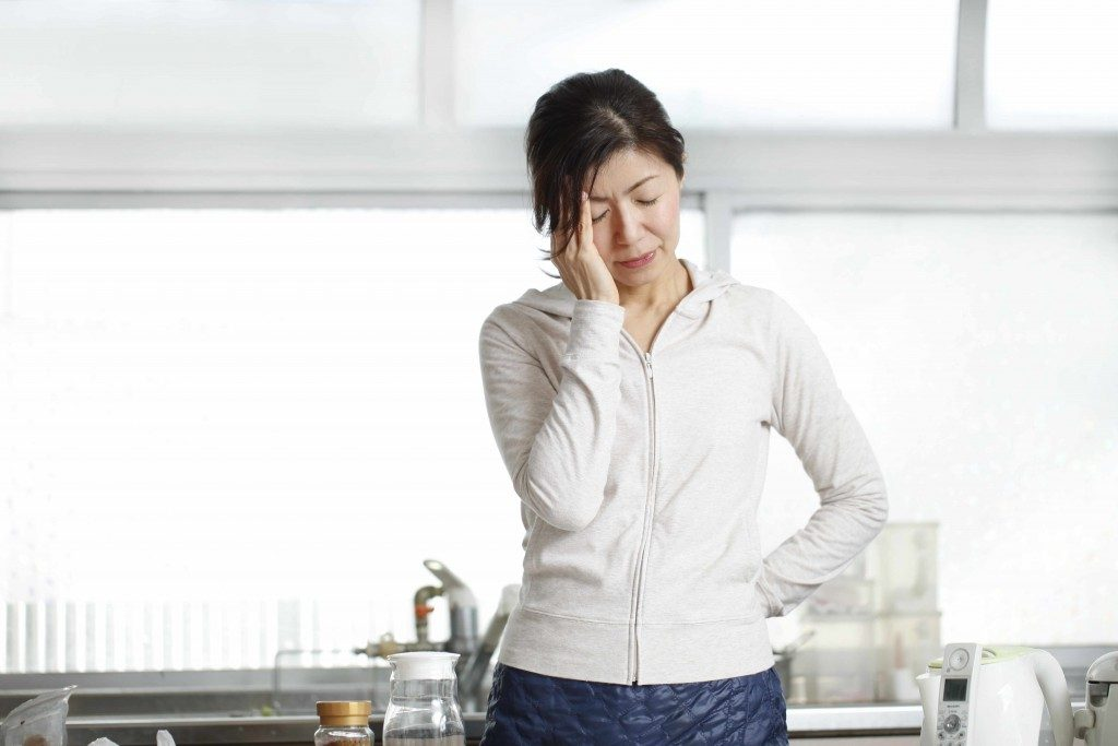 a woman with her head down and rubbing her forehead because of stress, headache, migraine or being tired