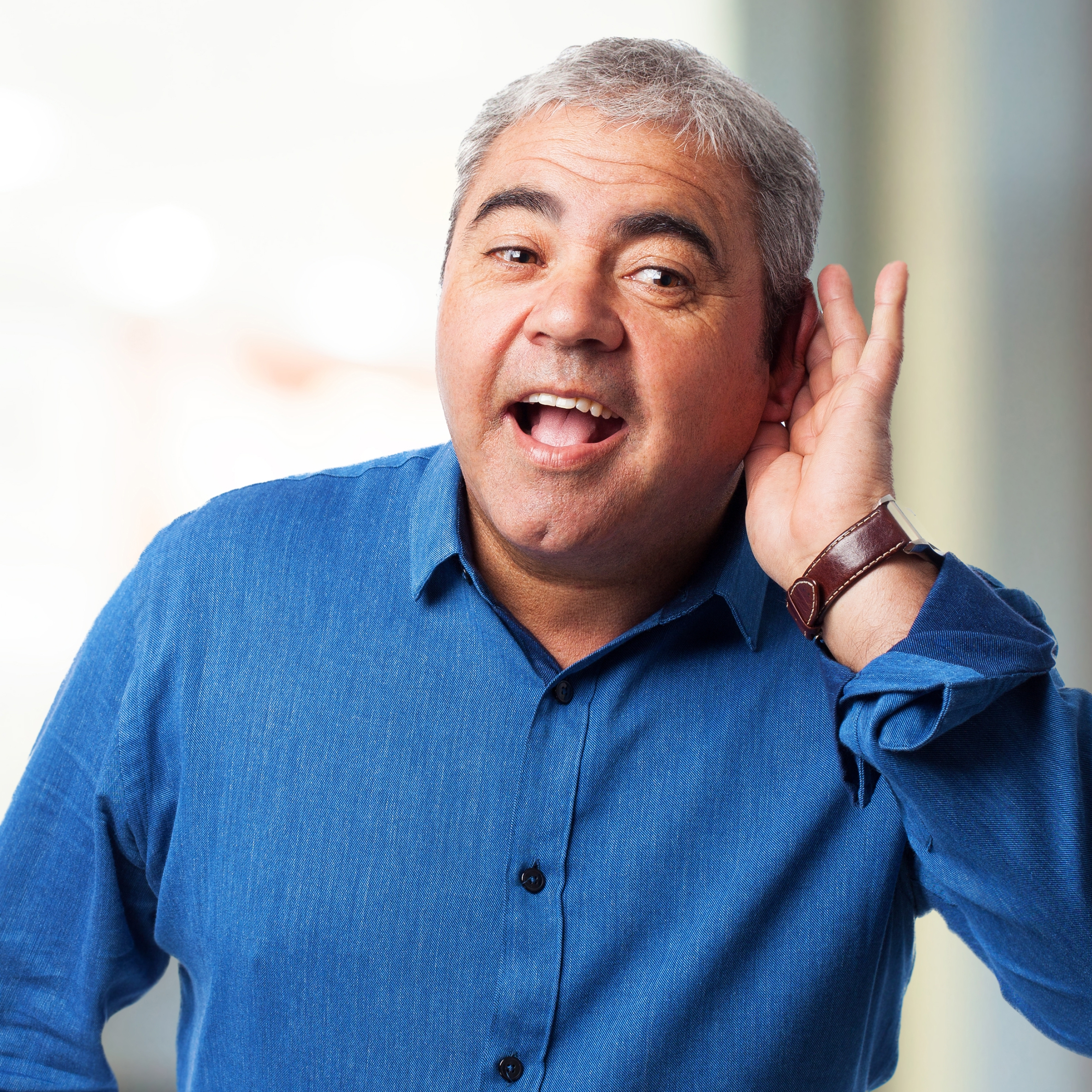 a middle-aged man holding his hand to his ear, trying to listen and hear something