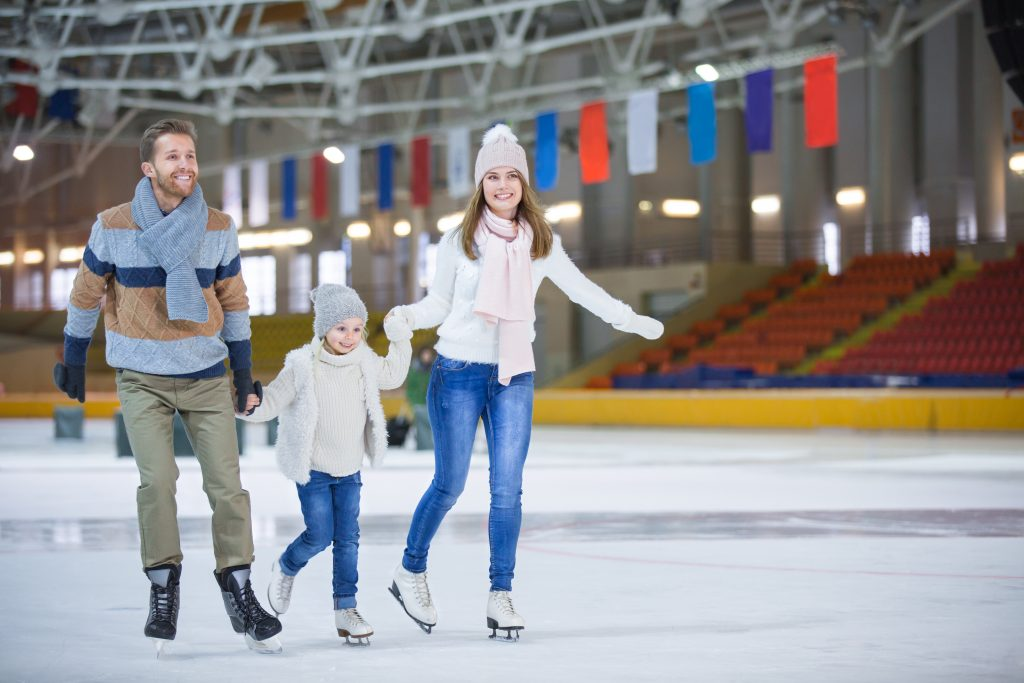 a smiling young family holding hands and ice skating at an indoor rink