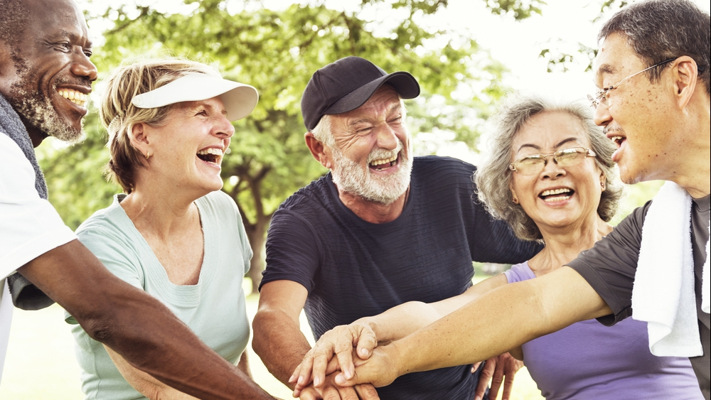 a diverse group of senior or retired friends exercising, joining hands, laughing and smiling