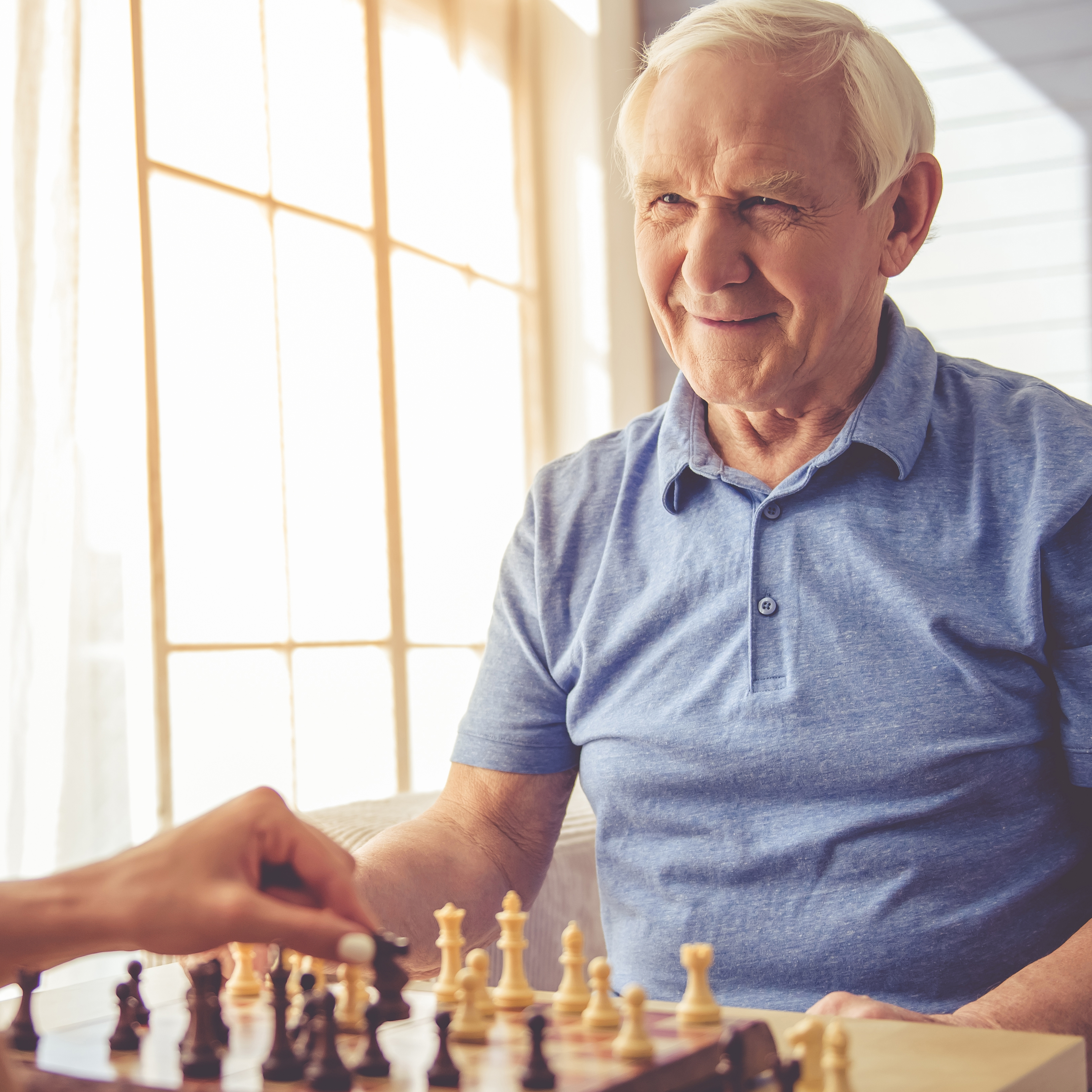 an older man playing a board game of chess with a young person