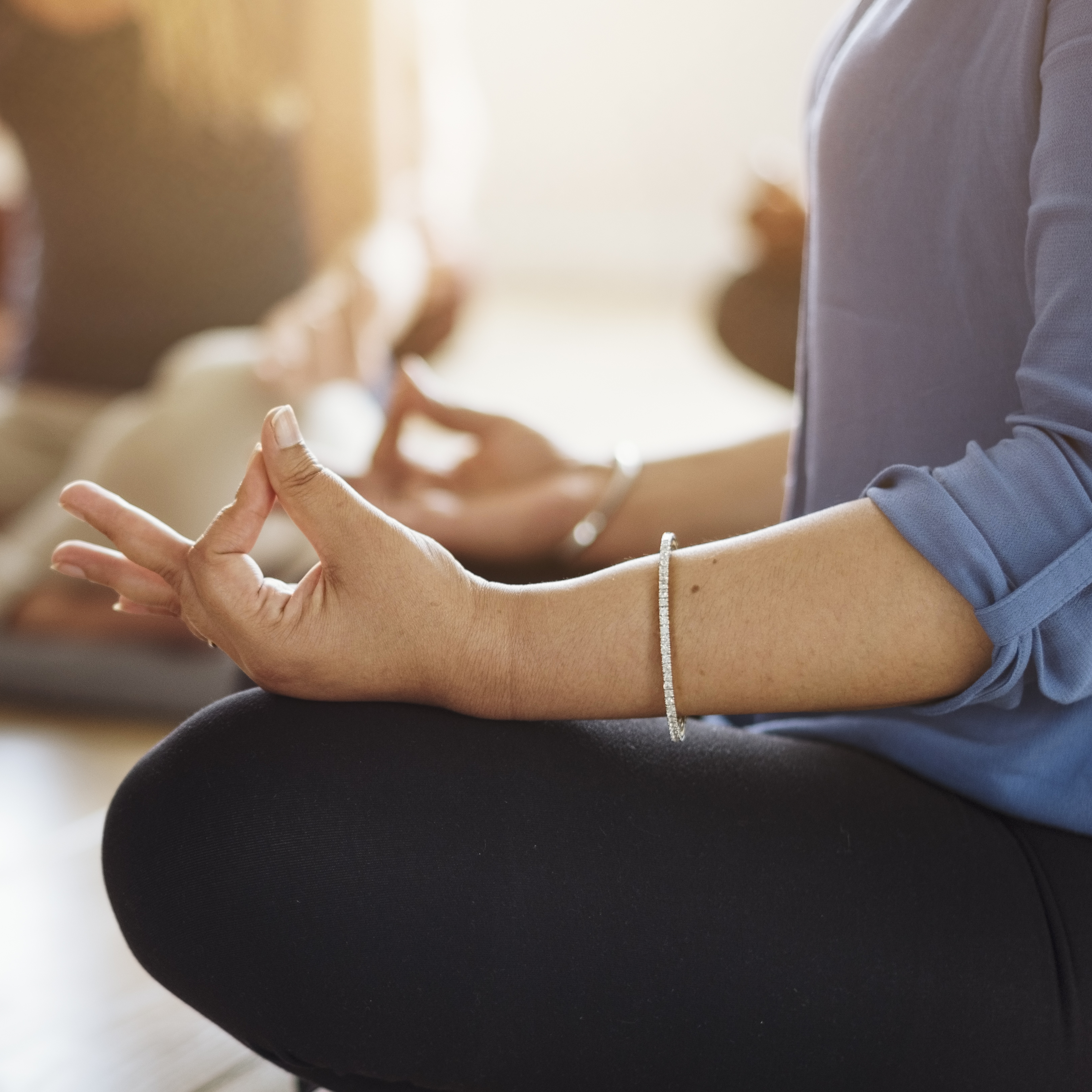 a middle-aged woman sitting in a mindful relaxed yoga pose