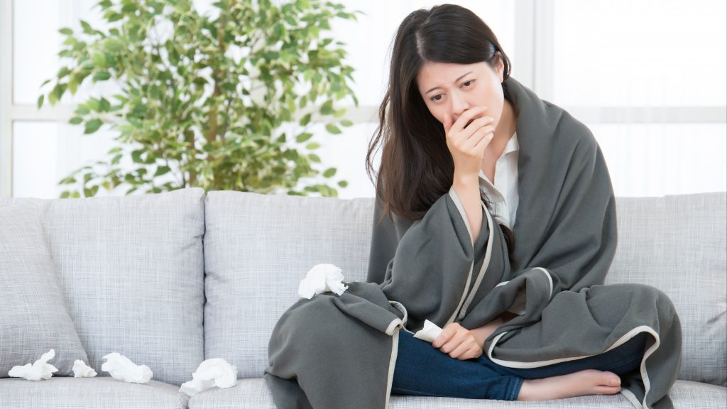 a young woman sitting on a couch, wrapped in a blanket who is looking sick