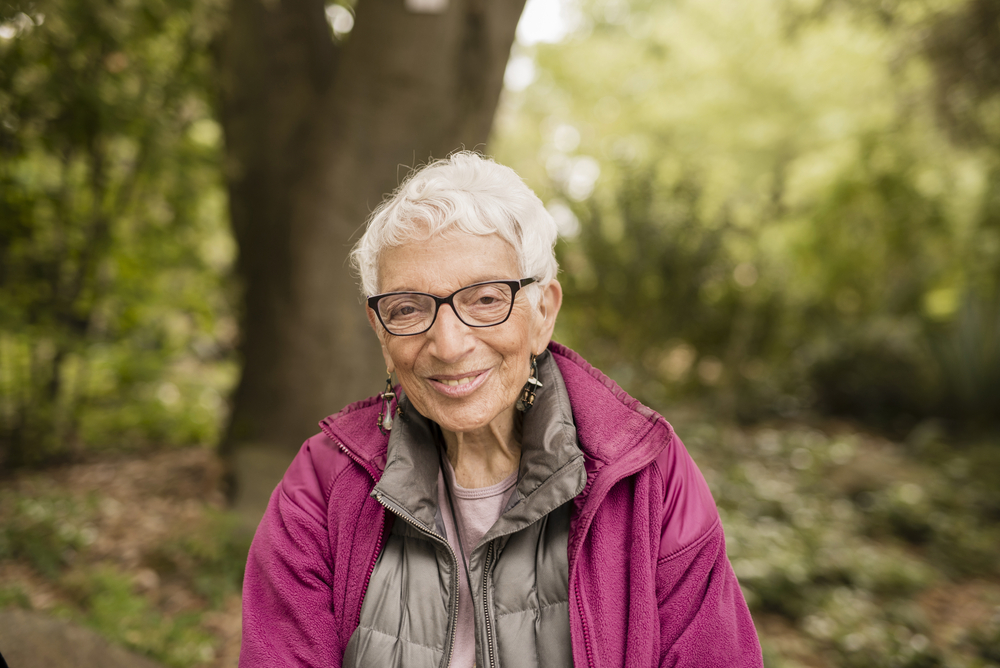 a smiling older woman outdoors