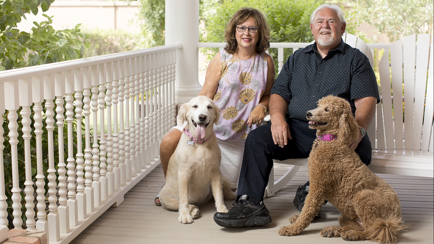 Susan and Tom Gus sitting on a porch with their dogs