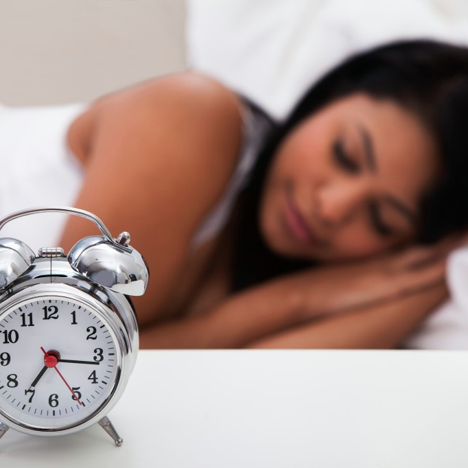 Alarm clock on bedside table and woman asleep