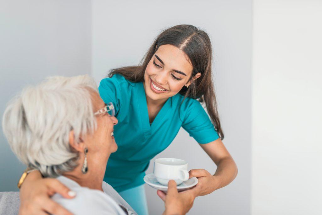 Una mujer joven que cuida esmeradamente a una anciana le sonríe mientras le ofrece café.