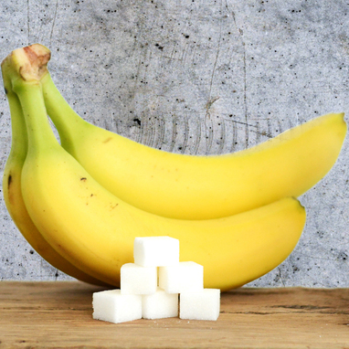 a bunch of bananas with a pile of sugar cubes, illustrating the sugar content