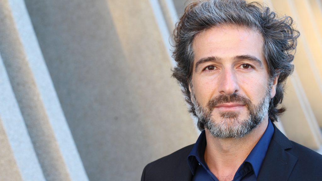 Imagen de un hombre de mediana edad y aspecto serio con barba y cabello grises