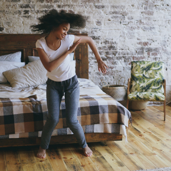 a happy, joyful Black young woman excited and dancing in her bedroom