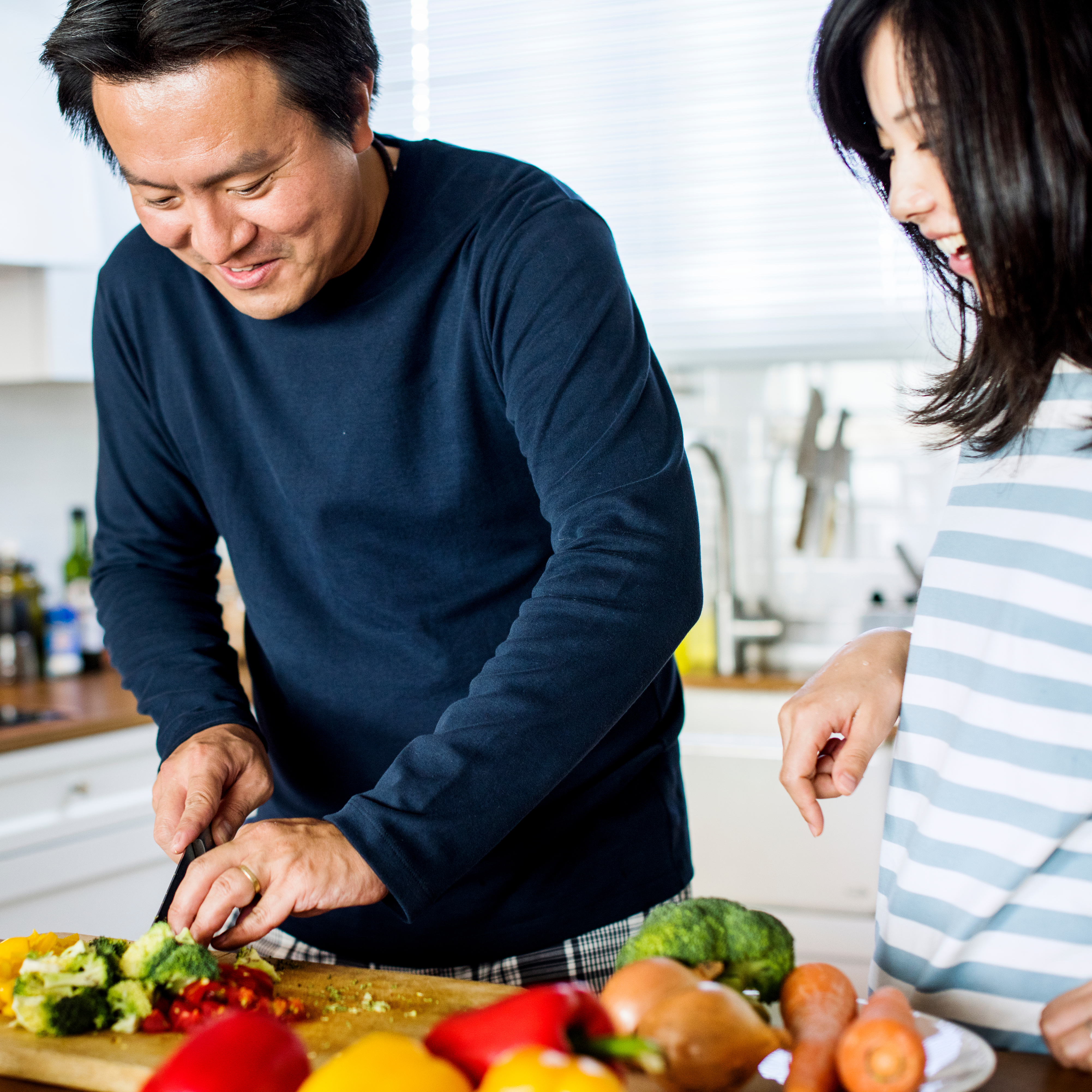 a smiling young couple in the kitchen, preparing food and cooking together