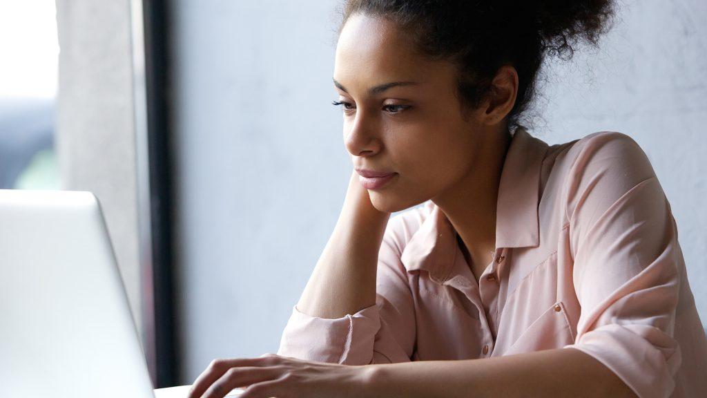 Una joven mujer leyendo información en la pantalla de un portátil, mirando pensativo, serio