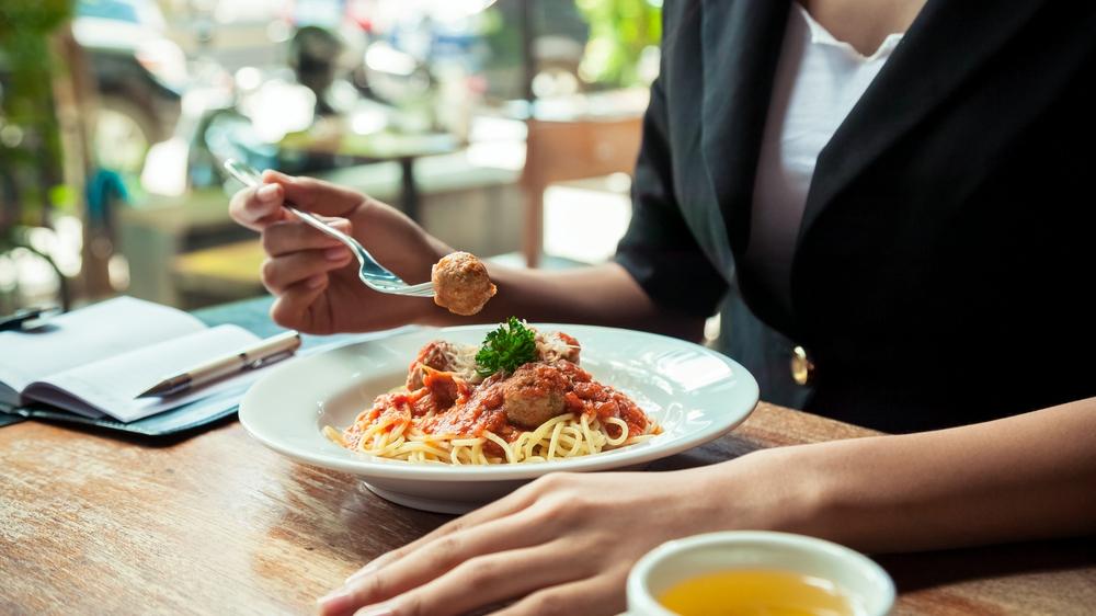 Una mujer come fideos con albóndigas y tiene un cuaderno junto al plato