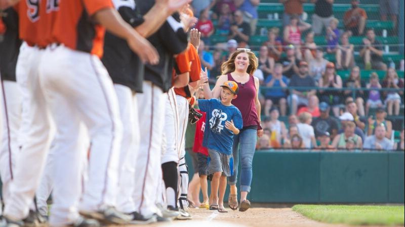 cervical cancer patient Megan Brooks walking on the baseball field